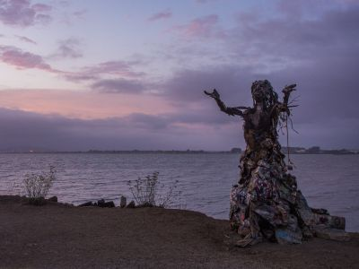 a sunset at albany bulb overlooking the san francisco bay with a statue of a person at the foreground. the person is made of found materials and appears to have arms outstretched with palms facing upwards. the person appears to be wearing a long flowing skirt