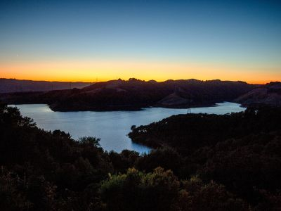 an overhead view of the briones reservoir at sunset. the water appears also silver in the blue and orange light of the evening