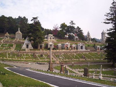 a well manicured lawn is spotted with gravestones of many shapes, sizes, and materials at mountain view cemetery. some are large enough to be small buildings