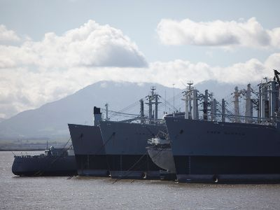 several large ships are anchored close together in suisun bay, members of the ghost fleet.