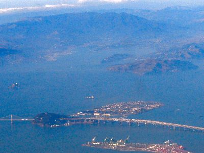an overhead view of Treasure Island and the Bay Bridge from way above. In the background Angel Island and the North Bay are visible