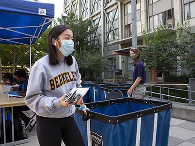 student moving in to the dorms wearing a mask during covid